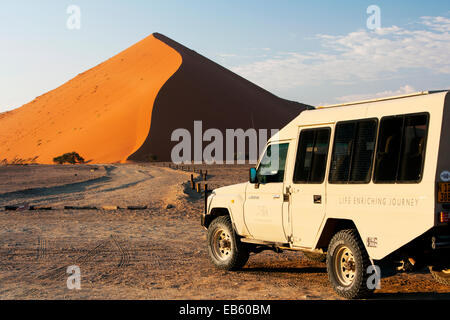 Safari Vehicle and Sand Dune in Sossusvlei National Park - Namib-Naukluft National Park, Namibia, Africa - Stock Photo