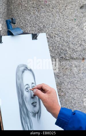 Close view of an artist´s hand drawing a portrait. Plaza Mayor, Madrid, Spain. - Stock Photo