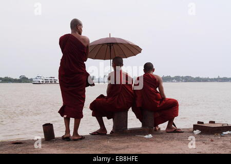 Two buddhistic monks sitting next to each other with umbrella and one buddhistic monk standing in front jetty yangon - Stock Photo