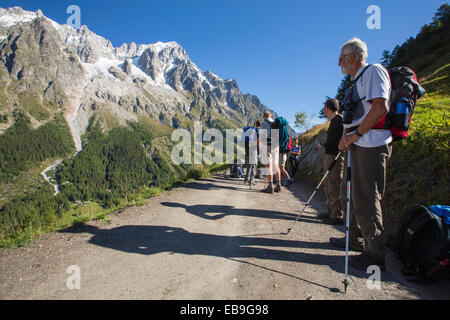 Walkers doing the Tour du Mont Blanc on Mont de la Saxe above courmayeur in Italy. - Stock Photo
