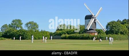 Iconic quintessential England idyllic village green cricket match bowler batsman & fielders Mountnessing Post Mill - Stock Photo