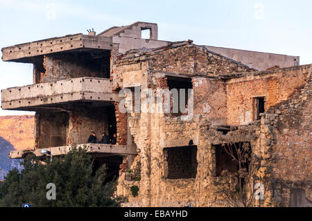 Men sit in an upper floor of a war damaged building in Mostar, Bosnia and Herzegovina - Stock Photo