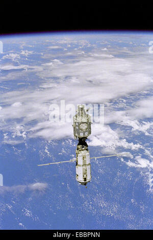View of the ISS during Flyaround. Backdropped against white clouds and blue ocean waters, the International Space - Stock Photo