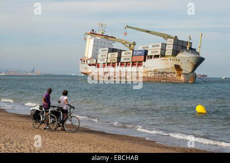 Cyclists looking the boat beached on the sand, El Saler, Valencia, Spain, Europe - Stock Photo