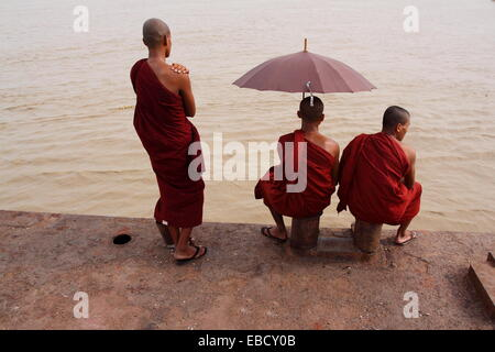 Two buddhistic monks sitting next to each other with umbrella, and one buddhistic monk standing in front of jetty, - Stock Photo