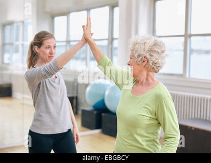 Senior woman giving high five to her personal trainer at gym. Excited old woman rejoicing health success with her - Stock Photo