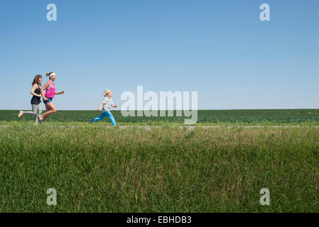 Three people running through field - Stock Photo