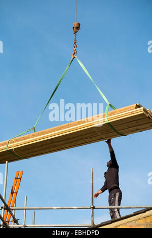 Timber being delivered by crane to a worker builder on scaffolding & Victorian terraced house roof. Looks like the - Stock Photo