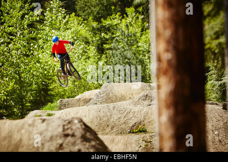 Young female bmx biker jumping mid air from rocks in forest - Stock Photo