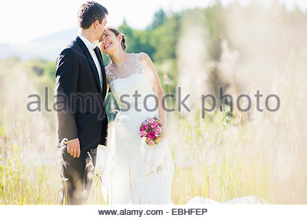 Candid portrait of bride and bridegroom in field - Stock Photo