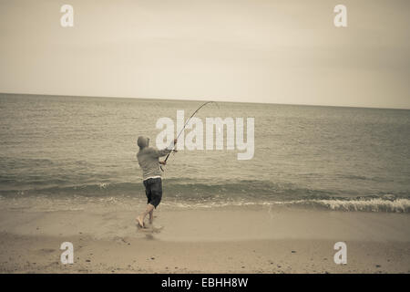 Fisherman casting fishing rod on beach, Truro, Massachusetts, Cape Cod, USA - Stock Photo