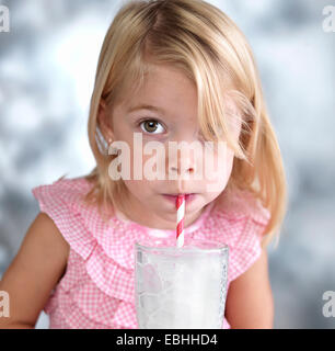 Portrait of female toddler blowing bubbles in milk through drinking straw - Stock Photo