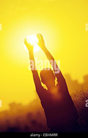 Woman touching sunset - Silhouette - Stock Photo