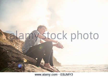 Teenage boy sitting on rocks - Stock Photo