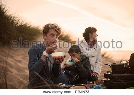 Mother with two boys eating food on beach - Stock Photo