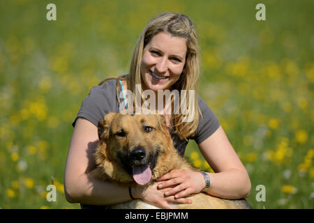 mixed breed dog (Canis lupus f. familiaris), young blond woman embracing her dog in a meadow, Germany - Stock Photo