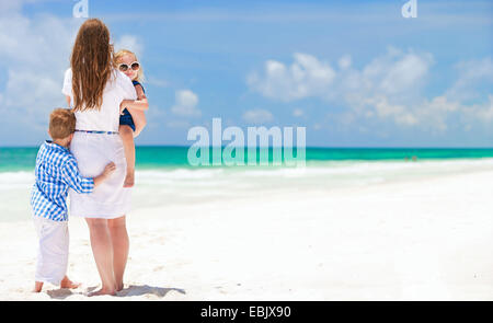 mother and two little children standing on sandy beach, Mexico - Stock Photo