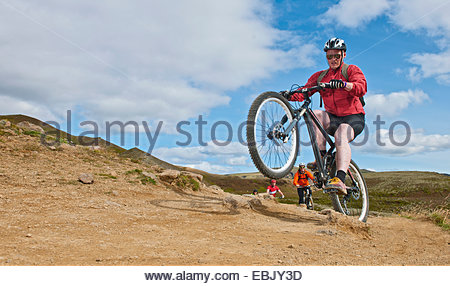 Mountain bikers cycling through Reykjadalur valley, South West Iceland - Stock Photo