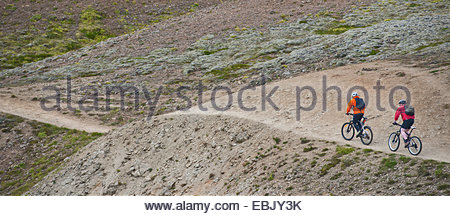 Two male mountain bikers cycling up dirt track, Reykjadalur valley, South West Iceland - Stock Photo