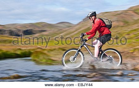 Young male mountain biker speed cycling through hot river, Reykjadalur valley, South West Iceland - Stock Photo