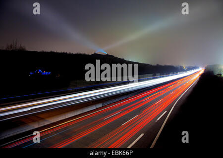 light streaks on motorway A2 in evening light and lights on stockpile Rungenberg, Germany, North Rhine-Westphalia, - Stock Photo