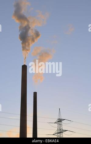 two chimney stacks smoking in the evening light in front of pylon, Germany, Bavaria, Stockstadt am Main - Stock Photo