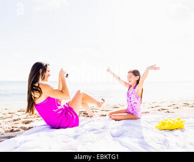 USA, Florida, Jupiter, Mom taking picture of her daughter (6-7) on beach - Stock Photo