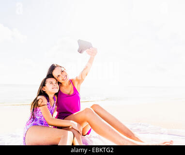 USA, Florida, Jupiter, Mom taking picture with her daughter (6-7) on beach - Stock Photo