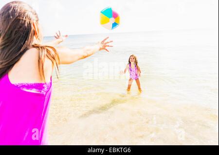 USA, Florida, Jupiter, Mom throwing beach ball to her daughter (6-7) on beach - Stock Photo