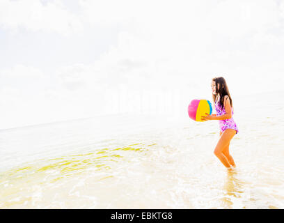 USA, Florida, Jupiter, Side view of girl (6-7) holding beach ball on beach - Stock Photo