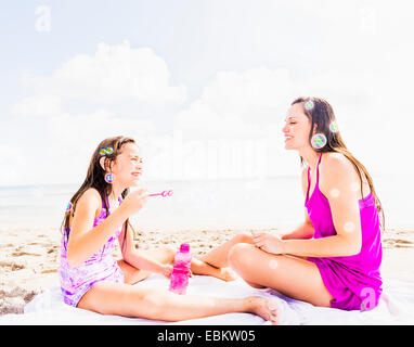 USA, Florida, Jupiter, Mom and her daughter (6-7) sitting on blanket on beach - Stock Photo