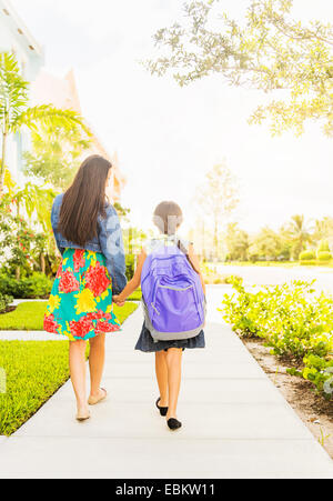 USA, Florida, Jupiter, Rear view of girl (6-7) holding hands with her mom outdoors - Stock Photo