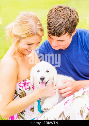 Portrait of young couple caressing white puppy - Stock Photo
