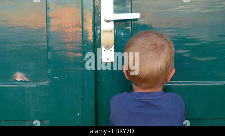 young boy standing in front of closed door sulking, Germany - Stock Photo