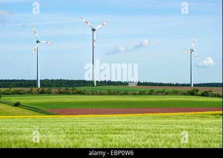 three wind wheels in field landscape in spring, Germany, Hesse - Stock Photo