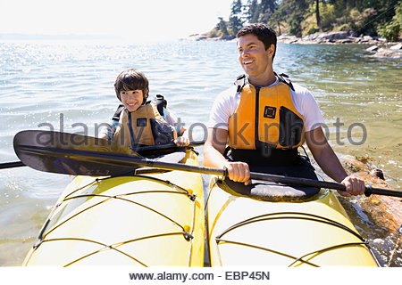 Father and son kayaking in ocean - Stock Photo