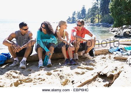 Runners sitting on sunny beach - Stock Photo