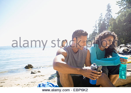 Runners sitting on sunny beach with water bottles - Stock Photo