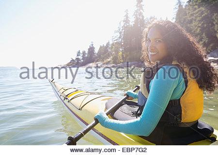 Portrait of smiling woman kayaking in ocean - Stock Photo