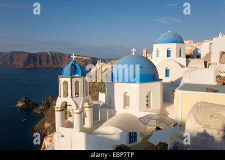 Ia, Santorini, South Aegean, Greece. Typical blue-domed churches clinging to hillside above the caldera. - Stock Photo