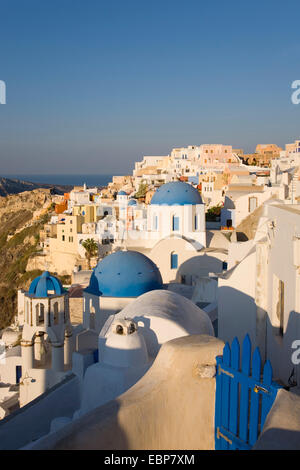 Ia, Santorini, South Aegean, Greece. The village at sunrise, typical blue-domed churches prominent. - Stock Photo