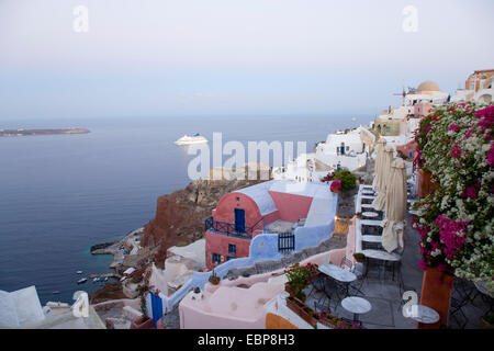 Ia, Santorini, South Aegean, Greece. Colourful houses clinging to hillside above Ammoudi Bay, dawn, cruise ship - Stock Photo