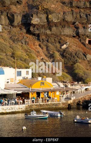 Ia, Santorini, South Aegean, Greece. Waterfront tavernas at Ammoudi Bay lit by the setting sun. - Stock Photo