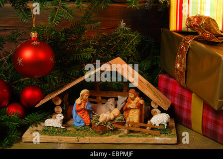 Nativity New Year's under the Christmas tree with ornaments - Stock Photo