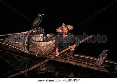 Cormorant fisherman with goatee and bamboo hat on bamboo raft with his two birds on the Li River at night, China, - Stock Photo