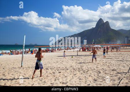 People playing tennis on Ipanema beach at dawn, Rio de Janeiro, Brazil, South America - Stock Photo