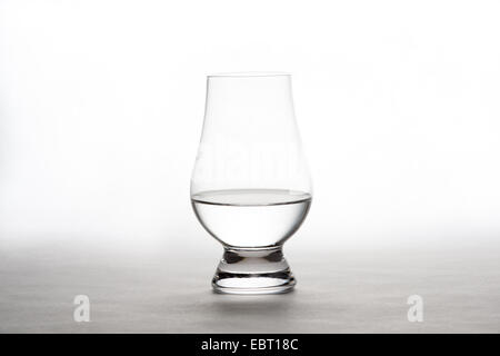 Single back-lit crystal glass containing vodka, gin, or tequila.  White background with copy space in upper part - Stock Photo
