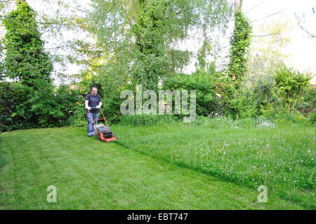 man mowing the lawn, Germany, Ruhr Area, Castrop-Rauxel - Stock Photo