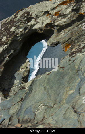 view through rock window to black beach of Nonza, France, Corsica, Cap Corse - Stock Photo