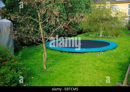 trampoline in garden, Germany - Stock Photo